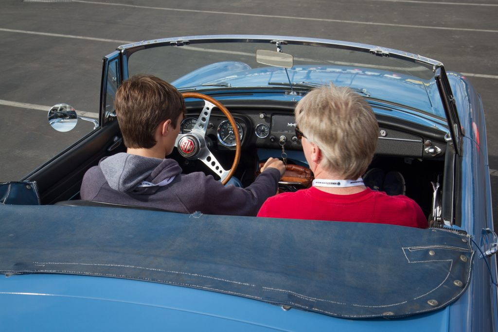 young boy learning to drive a classic car