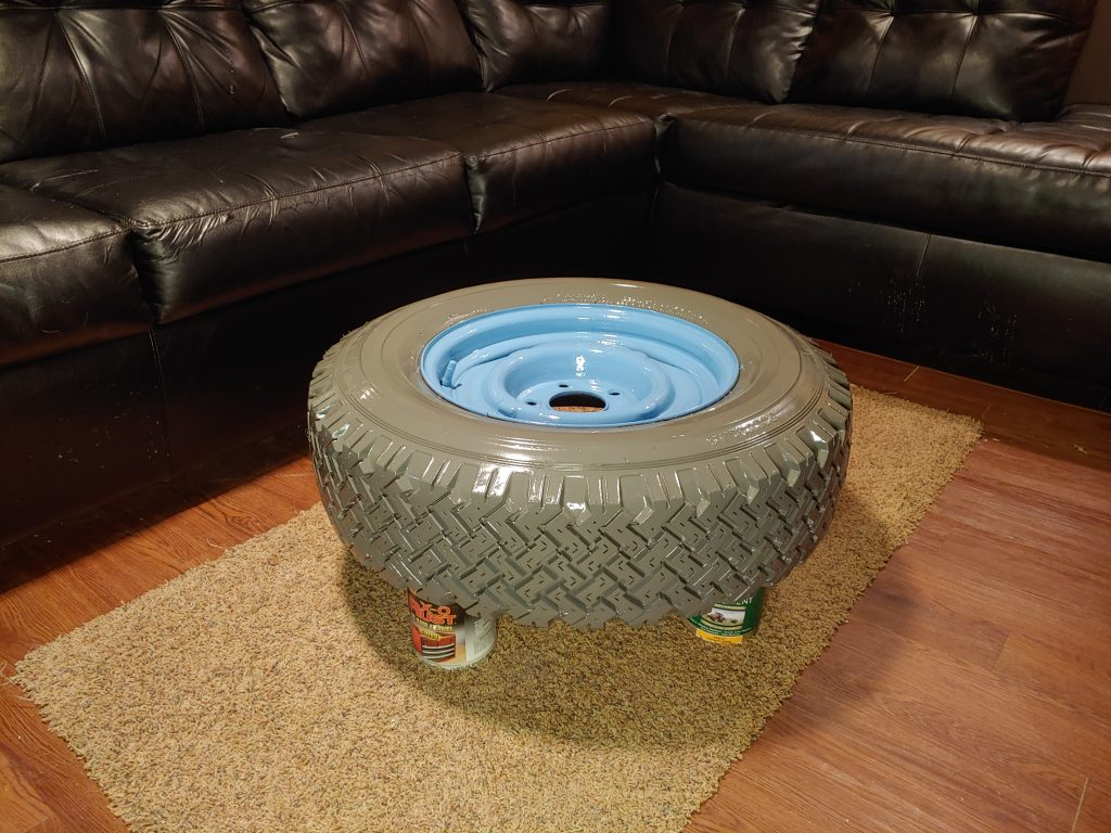 painted tire and wheel sitting on 4 paint cans