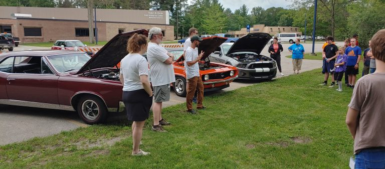 4 adults teaching kids about old cars